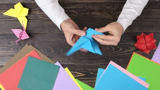 Man doing origami crane, top view. Colored paper sheets and origami figures. Japanese art workshop.