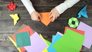 Man doing origami, fast motion. Male hands folding paper sheet to make a figure on wooden table, top view. How to make gifts at home.