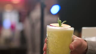 Man drinking yellow exotic cocktail in the bar. Alcohol drink beautified with apple slice and mint.