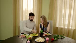 Man feeding woman grapes. Couple at the table laughing. How to make dating fun.