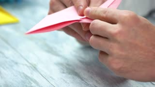 Man folding pink origami frog. How to make easy origami frog instructions. Japanese art of folding, crafts lesson.