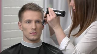Man getting a haircut. Barber woman using hair clipper.