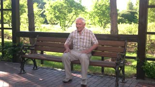 Man holding his back. Elderly guy on park bench. Consequences of operation on spine. Strong sharp pain.