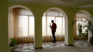 Man holding rose near window. Guy with flower standing indoor. Waiting for girlfriend.