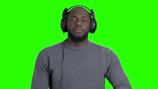 Man in headphones is dancing on green screen. Cheerful energetic african-american guy is listening to music, dancing and showing thumbs up on chroma key background.
