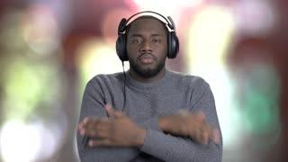 Man in headphones is listening to music. Handsome afro-american guy in headphones dancing on blurred background. Enjoy of good music.