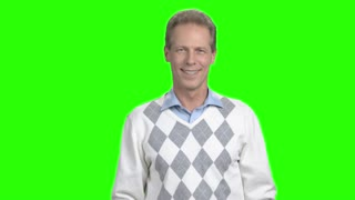 Man laughing on chroma key background. Mature man laughing and gesturing with hands on green screen. Human positive emotions.