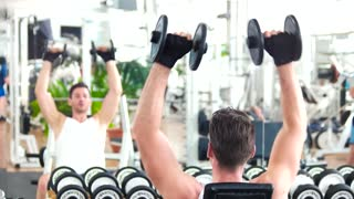 Man lifting dumbbells sitting on front of mirror. Young man lifting weight at gym.