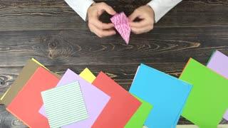 Man making patterned orizuru figurine. Traditional Japanese design of paper crane. Origami crafting workshop.