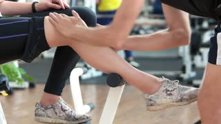 Man massaging injured female leg at gym. Woman sprained knee during fitness training. Fitness trainer massaging female leg.