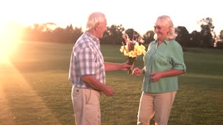 Man putting ring on woman. Senior couple with bouquet. This day is special. Celebrate the golden wedding.
