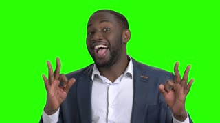 Man showing different gestures on green screen. Handsome afro american guy showing okey gestures on green screen. Angry businessman pointing with finger forward.