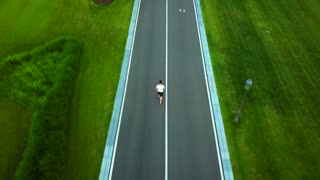 Man walking on the road, back view. Young sporty man on country road, drone view. Sporty walk in summer. Sport and healthy lifestyle.