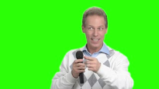 Man with a microphone speaking to the audience. Mature man with microphone having discussion with public and gesturing, green screen. Man speaking at conference.