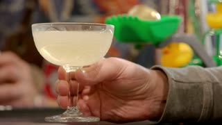 Man with alcohol drink in the glass. Close up male hand holding champagne saucer.