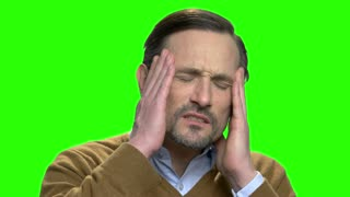 Man with headache massaging his temples. Green screen hromakey background for keying.