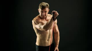Man with muscular body is training. Handsome athlete having workout with resistance band on black background. Sport achievements through maximum efforts.