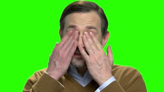 Man with tired eyes. Portrait of man rubbing his eyes. Green screen hromakey background for keying.