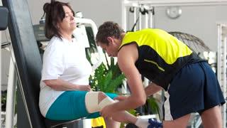 Man wrapping senior woman leg with bandage. Elderly woman injured leg when working out at gym. Compress for injured leg.