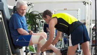 Man wrapping with bandage leg of elderly man. Man using elastic bandage to make compress to male leg at gym. Sport and healthcare.