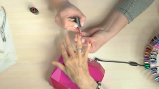 Manicure master professionally doing manicure. The process of red polish applying on aged woman nails by cosmetician in nail salon, top view.