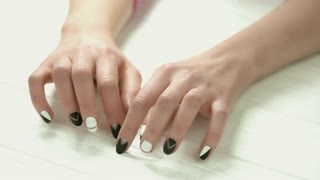 Manicured hands knocking on table. Young woman hands with black and white matte manicure close up.