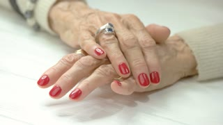 Manicured hands on table in beauty salon. Female aged finger nails with perfect red nails nervous knocking on table. Woman in a hurry.