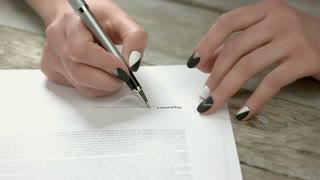 Manicured hands signing the document. Young woman hands with modern manicure signing important contract on old wooden background close up.