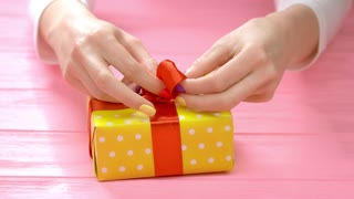 Manicured hands ties ribbon on gift box. Young woman with beautiful manicure packing gift box with red ribbon. Holidays and celebrations concept.