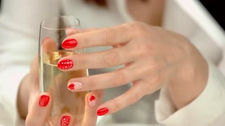Manicured hands with glass of champagne. Well-groomed hands of young woman with red manicured caress crystal glass with bubbly beverage, red petals on white silk.