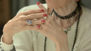 Manicured hands with luxury jewelry. Senior woman well-groomed hands with perfect red polish on nails.