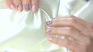 Manicured hands with silk, slow motion. Beatiful female hands with gentle manicure holding white silk fabric close up. Purity and tenderness concept.
