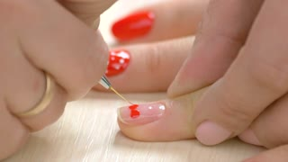 Manicurist drawing a heart on female nails. Nail master making design on client nails, fast motion. Woman receiving manicure in nail salon.