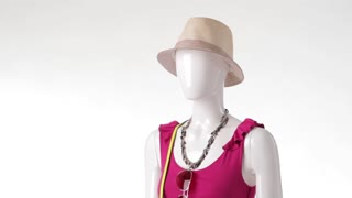 Mannequin in pink top turning. Beige headwear and sleeveless top. Bright clothing for young girls. Stylish hat on showcase.