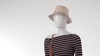 Mannequin in striped top turning. Long sleeve top and hat. Bicolor purse with beige headwear. Girl's clothing for warm season.