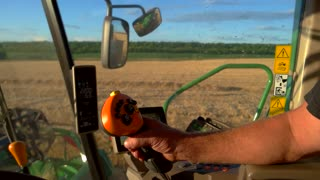 Man's hand on harvester controls. Machine is moving through field. Combine driver at work. Monthly plan is exceeded.