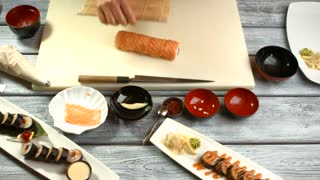 Man's hands make sushi. Long orange sushi roll. Traditions of japanese cuisine. Best student of cooking class.