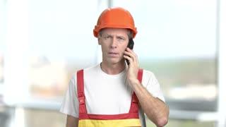 Mature architect talking on mobile phone. Caucasian builder in orange helmet using mobile phone on blurred background.