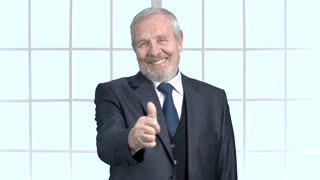 Mature businessman gesturing thumb up. Smiling bearded man in formal wear showing thumb up on window background. People, business and success concept.