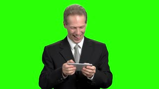 Mature businessman playing video games on smartphone. Infantile adult man in suit playing video games in green background.