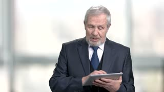Mature businessman talking at business presentation. Elderly man in business suit presents new project to colleagues using digital tablet. Senior businessman at business meeting.