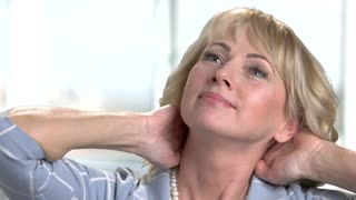 Mature businesswoman massaging her neck. Close up portrait of happy middle aged lady doing relaxing self massage for neck and shoulders.