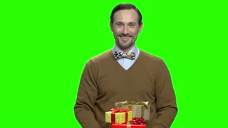 Mature caucasian man giving birthday presents. Green screen hromakey background for keying.