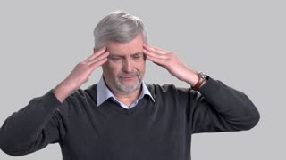 Mature caucasian man suffering from headache. Stressed man rubbing his temples because of strong headache on grey background. Portrait of overworked man with migraine.