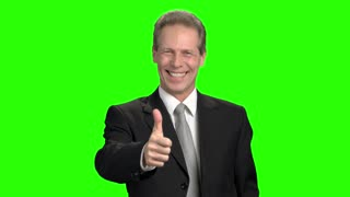 Mature clerk in suit shows thumb up. Cheerful man smiling with teeth and shows like, green hromakey background.