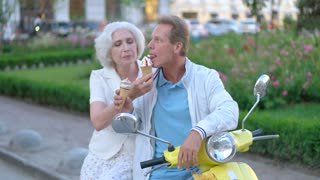 Mature couple eating ice cream. Two people laughing. Go on vacation in summer. Best time spent together.