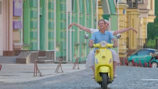 Mature couple is riding scooter. Woman smiling and waving arms. Feeling happy and free. Travel together this summer.