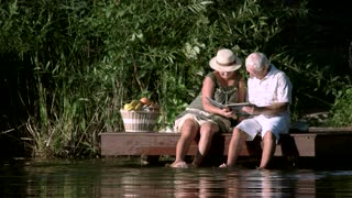 Mature couple looking at photo album. Old man and woman sitting with photo book near river.