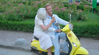 Mature couple sitting on scooter. Face smeared in ice cream. Feel no shyness. There's always time for jokes.