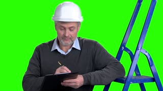 Mature male supervisor writing on clipboard. Senior constructor making a note on clipboard on Alpha Channel background.
